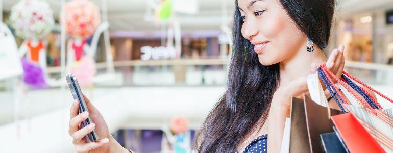 Fille avec un smartphone dans un magasin