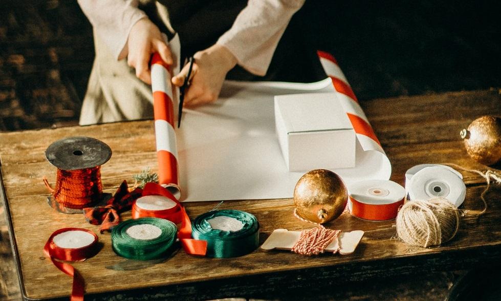 Personne en train d'emballer un cadeau de Noël source Pexel