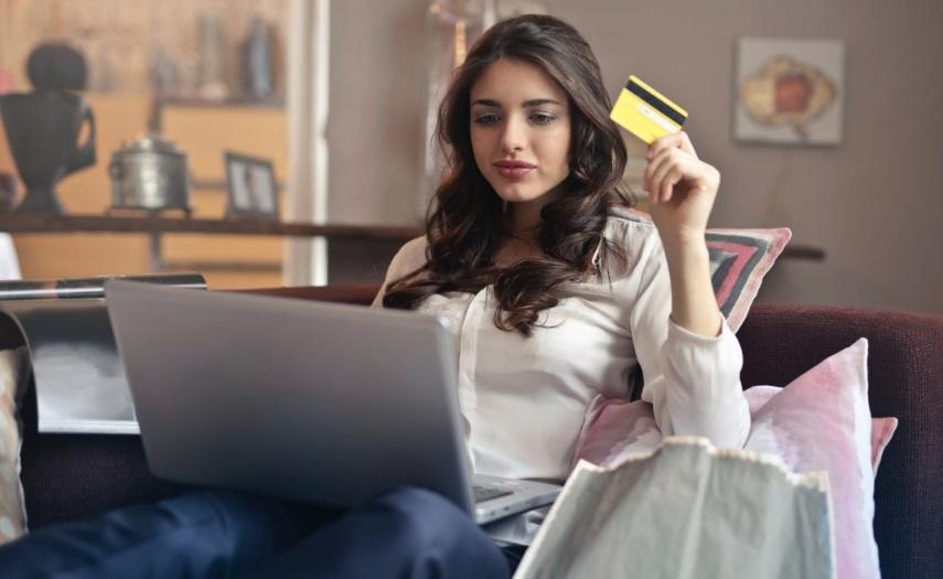Une femme devant son ordinateur avec carte bancaire
