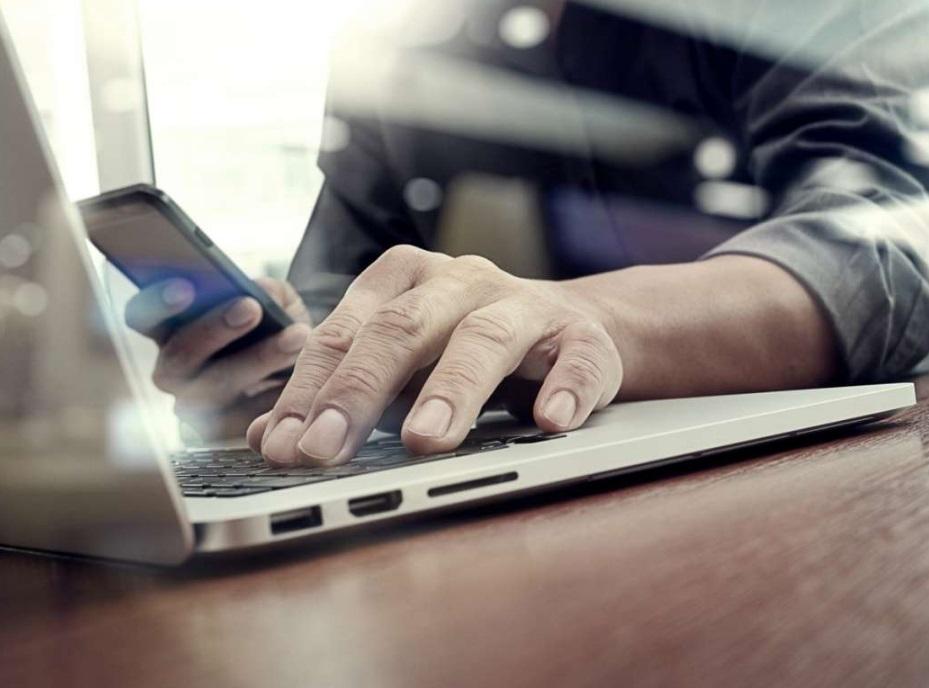 Homme sur un ordinateur et smartphone