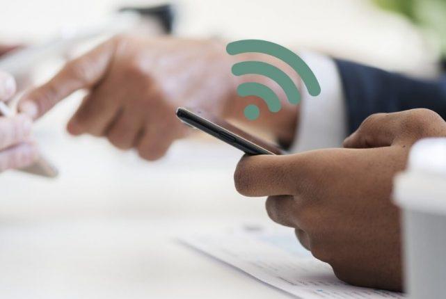Smartphone dans une main et sigle wifi