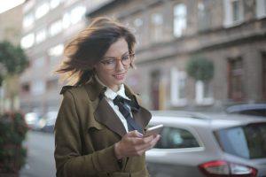 Une femme souriant devant un SMS