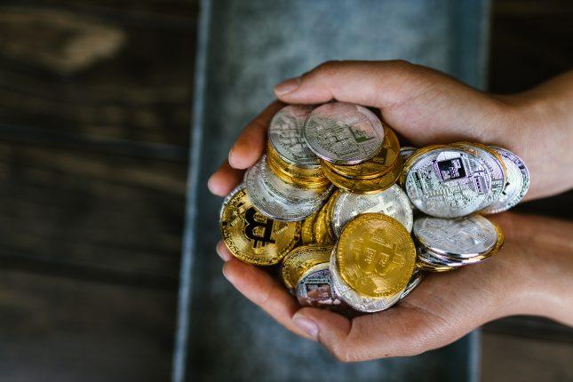mains pleine de crypto monnaie pièces